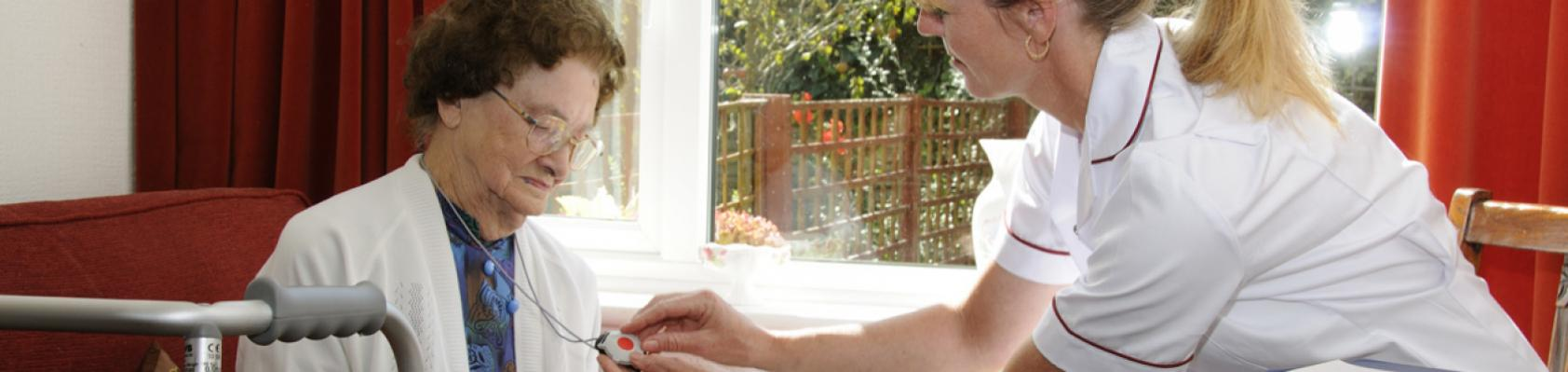A woman having her pendant alarm installed.